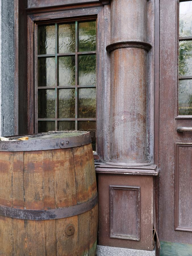 Old traditional pub / bar entrance with a brown whiskey barrel. Window, door, and weathered wooden wall royalty free stock photos