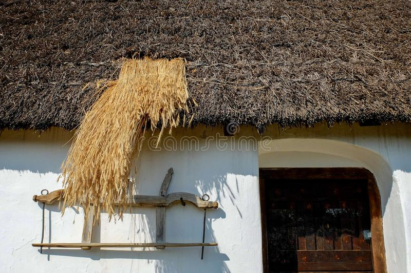 Old traditional thatch roof being mended. Old traditional rural thatch roof being mended with fresh thatch stock photos