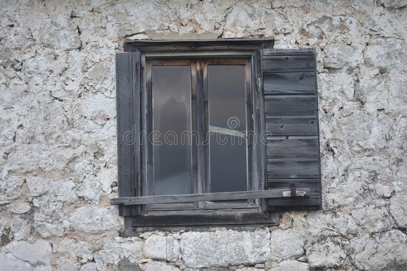 The old,traditional,stone house and the wooden window stock images