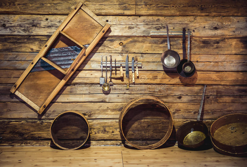 Old traditional utensils hanging on wooden wall at kitchen stock photography