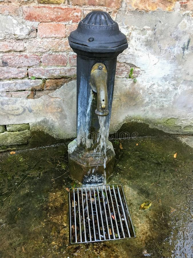 A old traditional water fountain found all over the city of Venice, Italy.  It supplies fresh cool drinking water. When you need water stock images