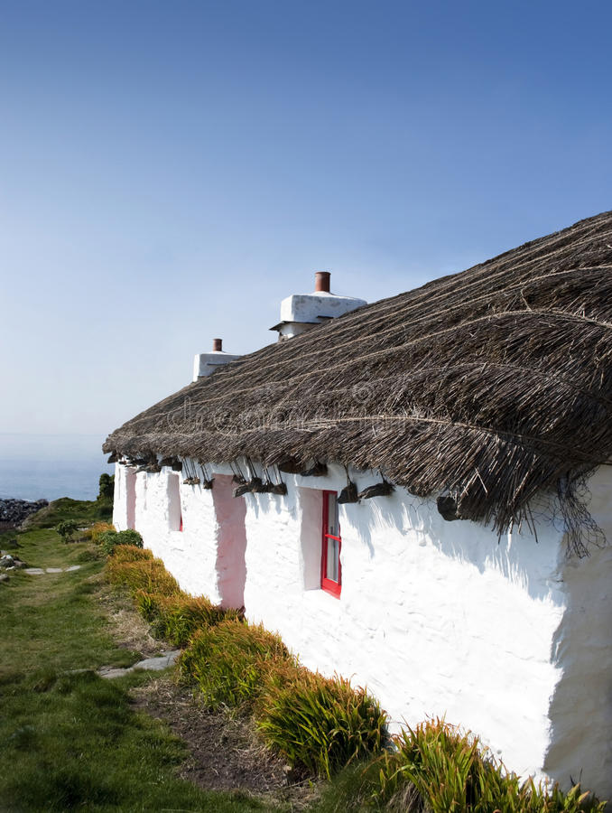 Old traditional white cottage with thatched roof