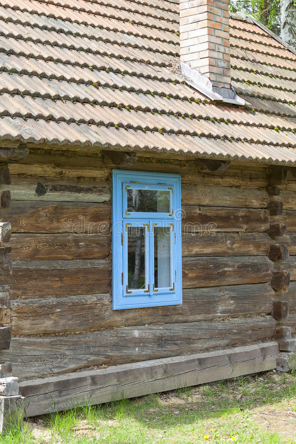 Old traditional wooden polish cottage in open-air museum, Kolbuszowa, Poland. Old traditional wooden polish cottage with blue window in open-air museum stock photo