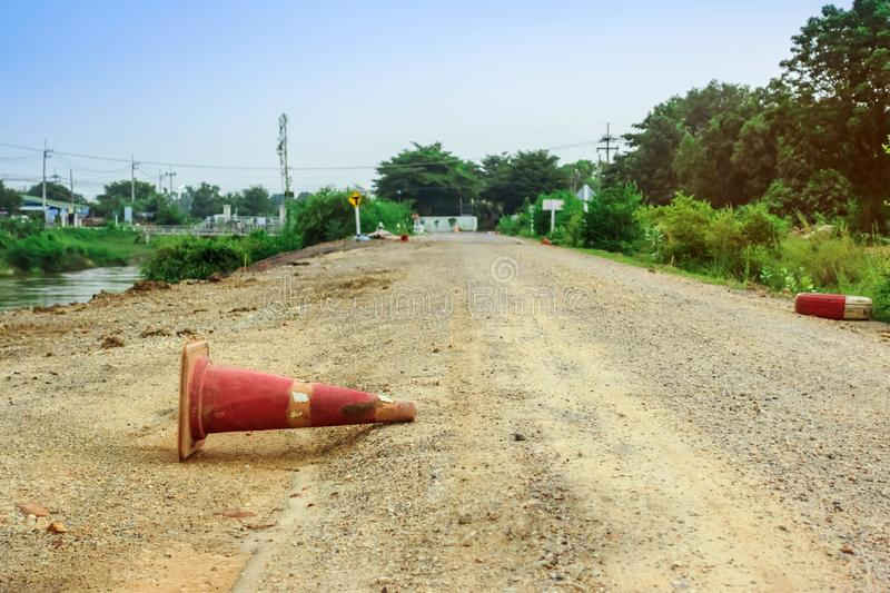 The old traffic cone falling on the road that was being repaired along the irrigation canal. For agriculture royalty free stock images