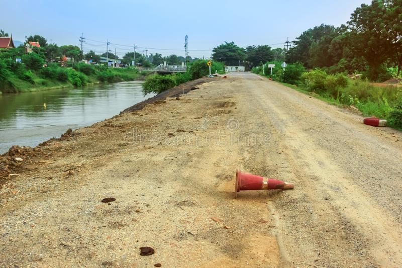 The old traffic cone falling on the road that was being repaired along the irrigation canal. For agriculture royalty free stock photos