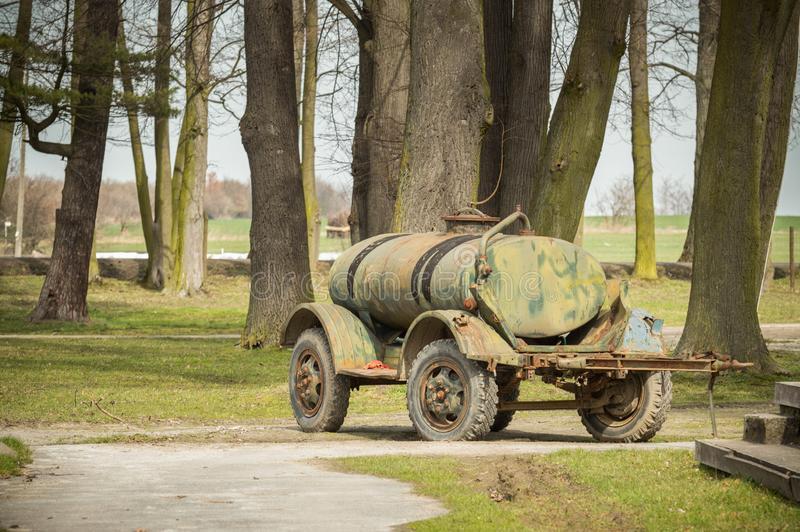 Old trailer, water tank for animals before trees. Poland, Old trailer, water tank for animals europe wheels trees path moro military grass plant royalty free stock image