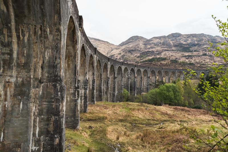 Old train railway arched bridge. Old train railway with arched bridge surrounded by trees with hills in view, Glennfinnan Viaduct, Scottish Highlands. on a stock image