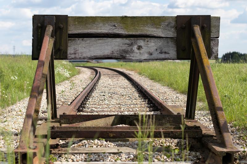 Old train tracks with a wooden stop device. Composition with leading lines. Wooden, old stock photos