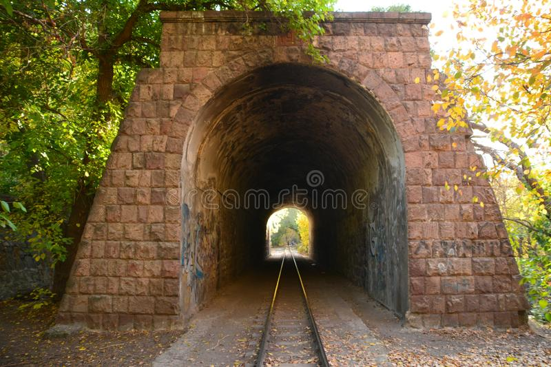 Old train tunnel with railway in a mountain. Beautiful forest photos and wallpapers royalty free stock photos