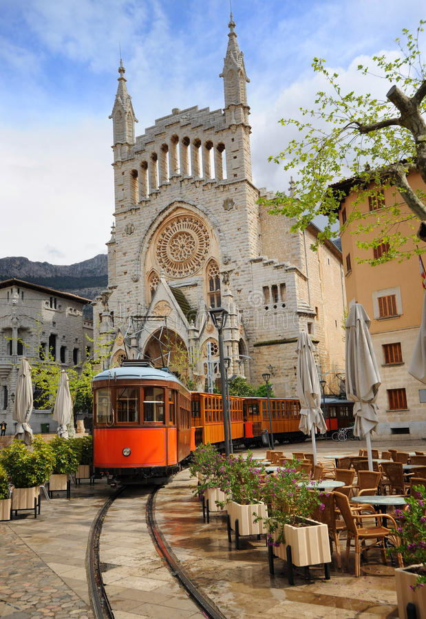 Old tram in front of the Cathedral of Soller, Mallorca, Spain. Old tram in the downtown of Soller in front of medieval gothic cathedral with huge rose window royalty free stock photos