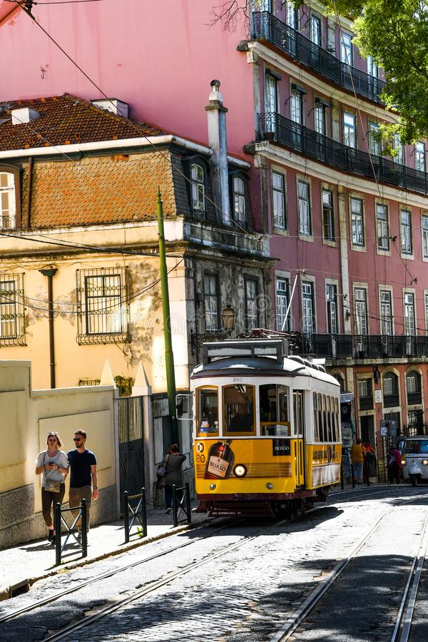 Old tram going through narrow streets in Lisbon royalty free stock images