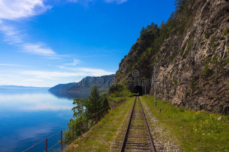Old Trans Siberian railway on lake Baikal. Old stone tunnel in mountain the rock on the Circum-Baikal railway. Awe background of a summer landscape with stock images