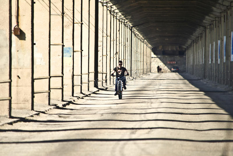 Old transport bridge with concrete columns and cyclist rides royalty free stock photography