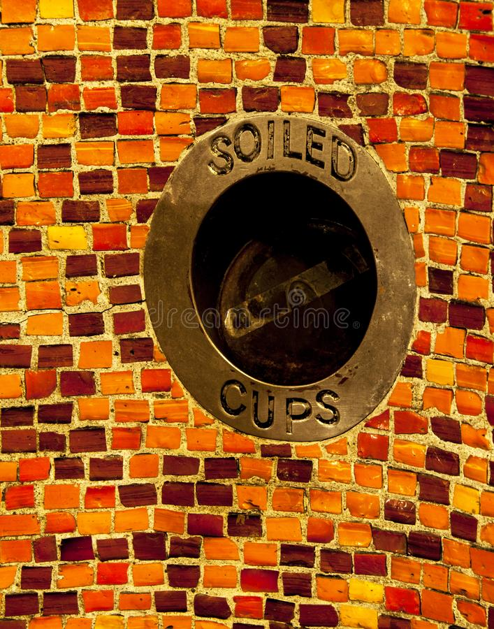 Soiled cups trash receptacle in tiled wall. text royalty free stock photos