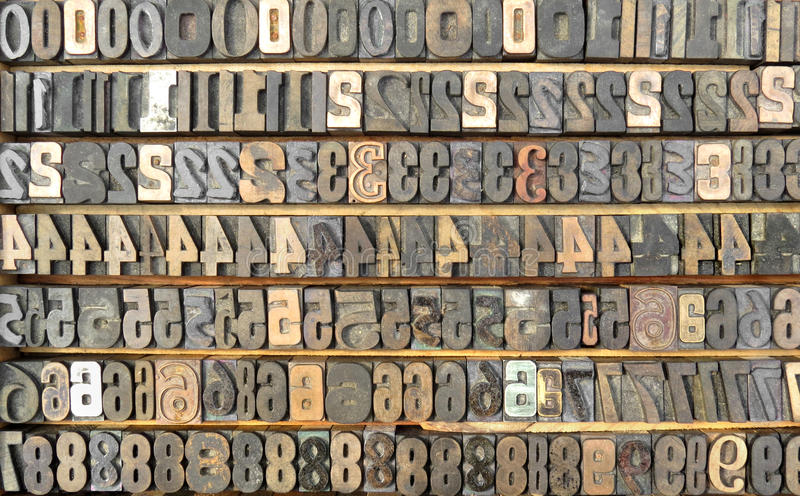 Old tray of typeset numbers. stock photo