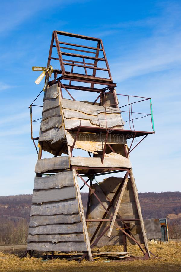 Old triangular metal structure upholstered wooden board stands in mountains on background forest. Under blue boundless sky stock images