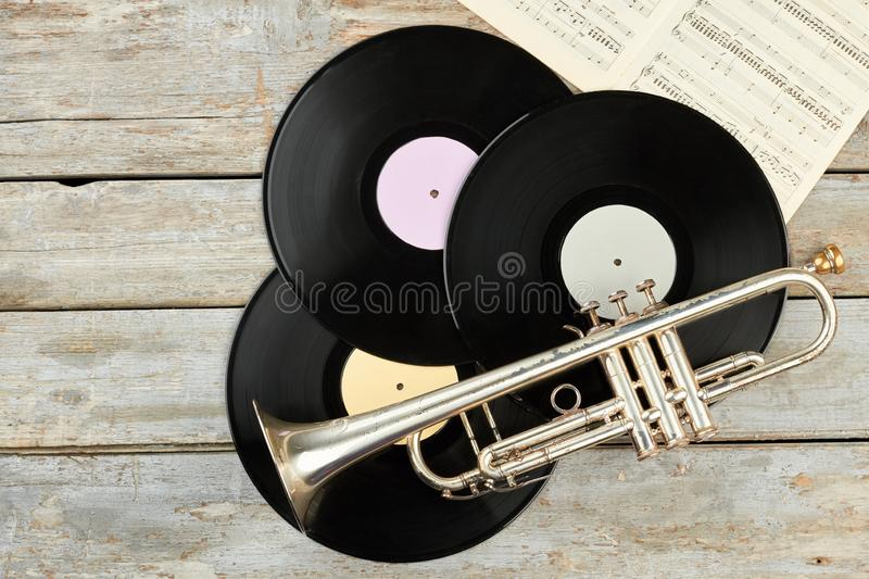 Old trumpet and vinyl records on wooden background. royalty free stock photography