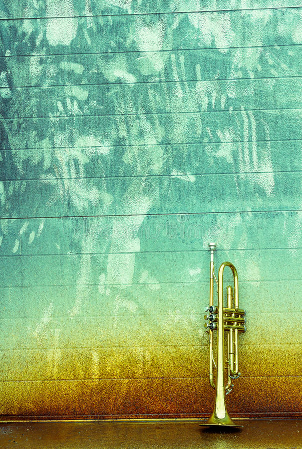 Old Trumpet. Old worn trumpet stands alone against a grungy wall outside a jazz club stock photography