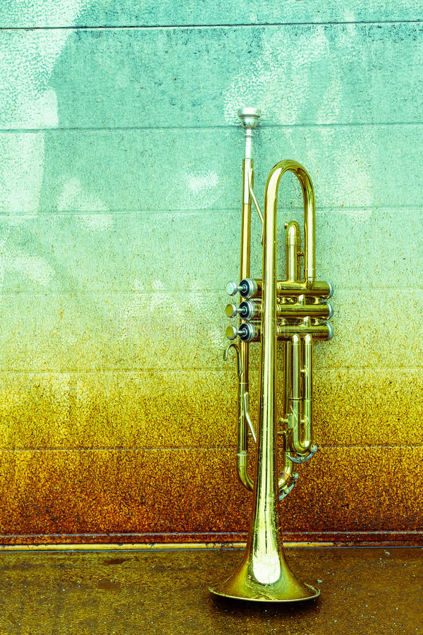 Old Trumpet. Old worn trumpet stands alone against a grungy wall outside a jazz club stock photo