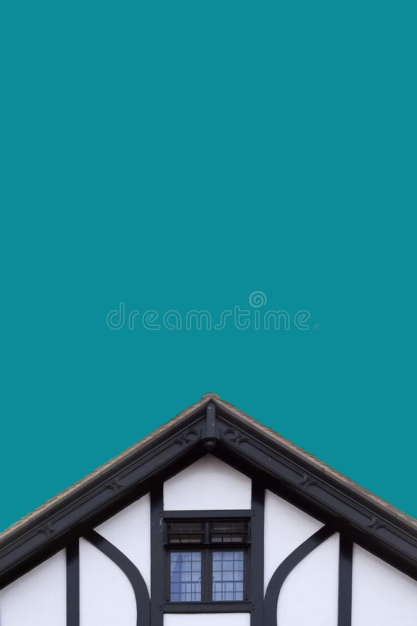 Old Tudor building roof. Top of an old Tudor building showing the roof and small window royalty free stock photo