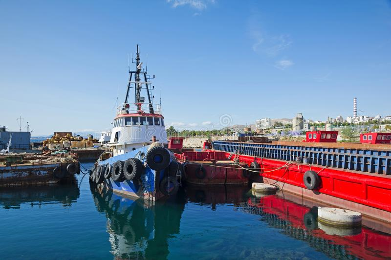 Old tugboat and barges at Piraeus stock image