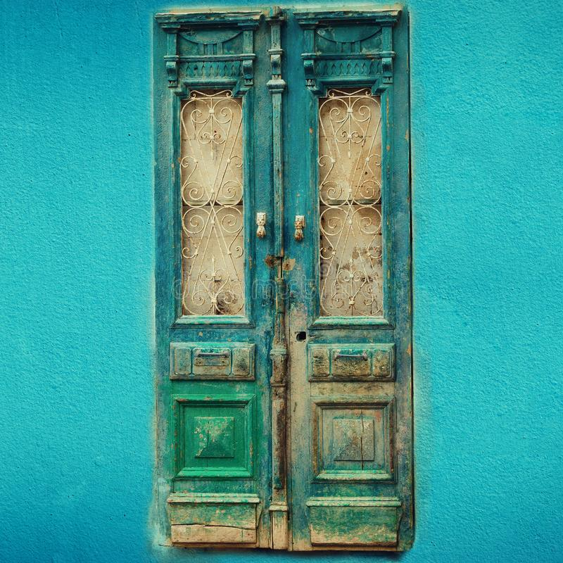Old turquoise wooden door on blue wall with copy space. Texture background. Pop art concept, vintage style. Square crop.  royalty free stock photo