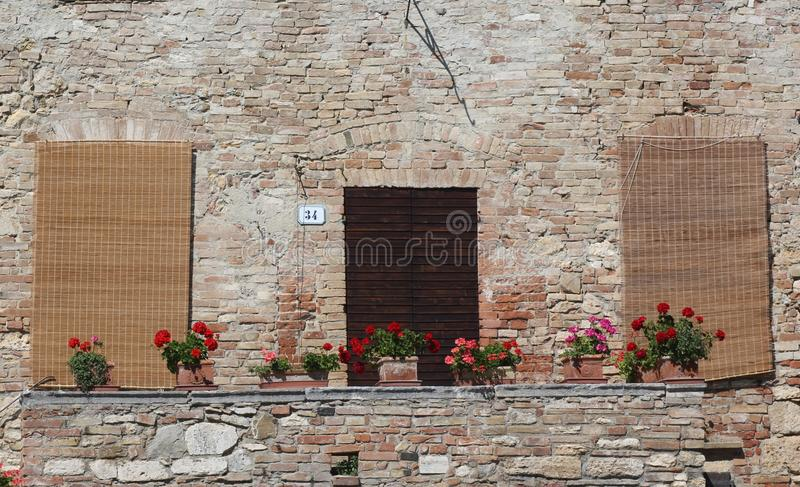 Old Tuscan villa with bamboo screens over the windows. Old Tuscan villa in the hot sun with bamboo screens shading the windows and plants pots on a wall stock photos