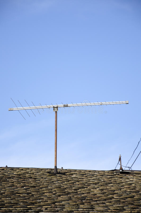 OLD TV ANTENNA. Old television antenna on old roof, obsolete technology. Signal stock photo