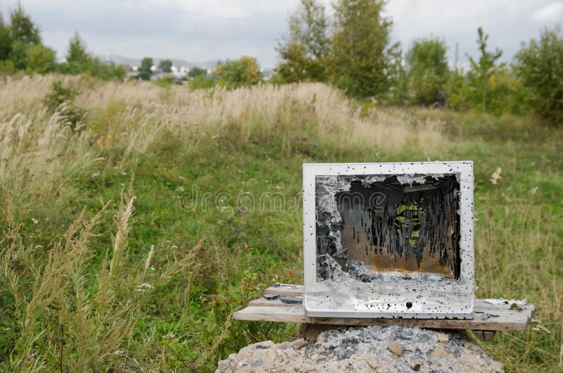 Old TV with broken screen shot from pneumatic weapon against background of green grass and trees. fun for farmers concept - image stock photo