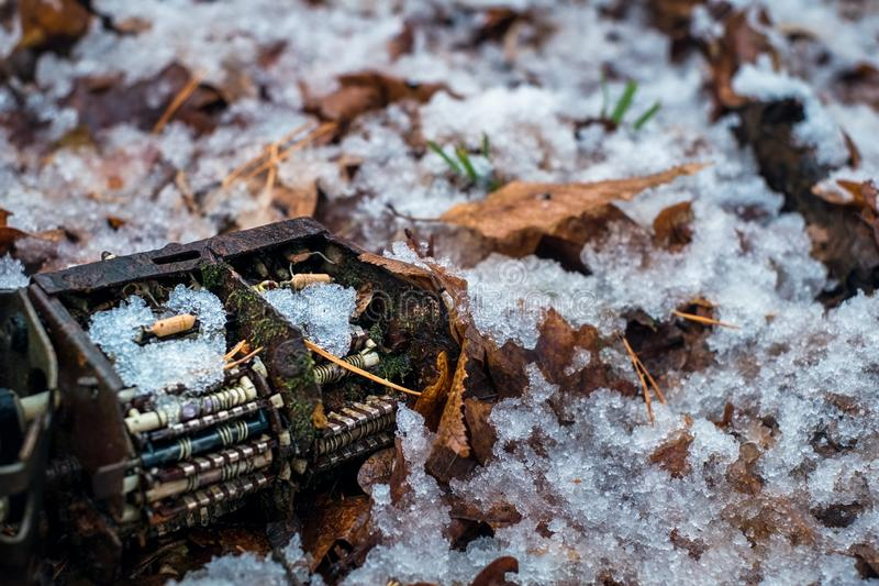 Old tv tuner channel selector with moss and snow in the forest stock photography