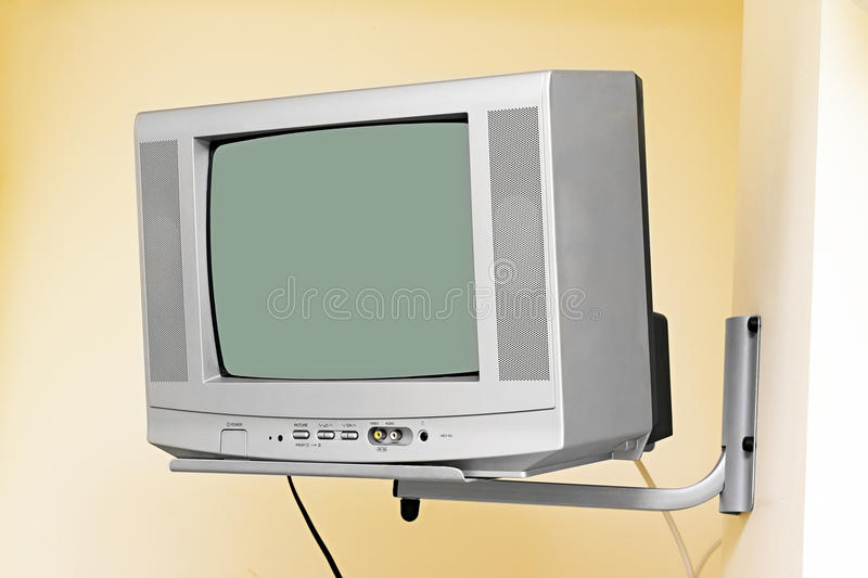 An old TV on the wall. Old small TV mounted on wall bracket stock image