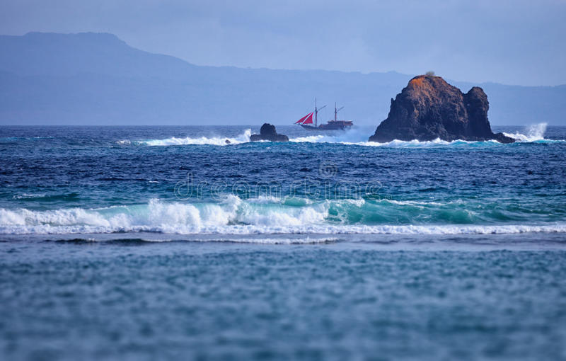 Old two-masted schooner near the rocks in the sea. Indonesia, Ba stock photo