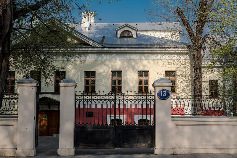 Old two-storey building number 13 in the center of Moscow, Russia. Entrance to the territory with black iron gates.  royalty free stock photo