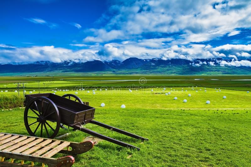 Old two-wheeled cart. Old wooden sledge and two-wheeled cart on the lawn. The reconstituted village - Museum Vikings in Iceland stock image