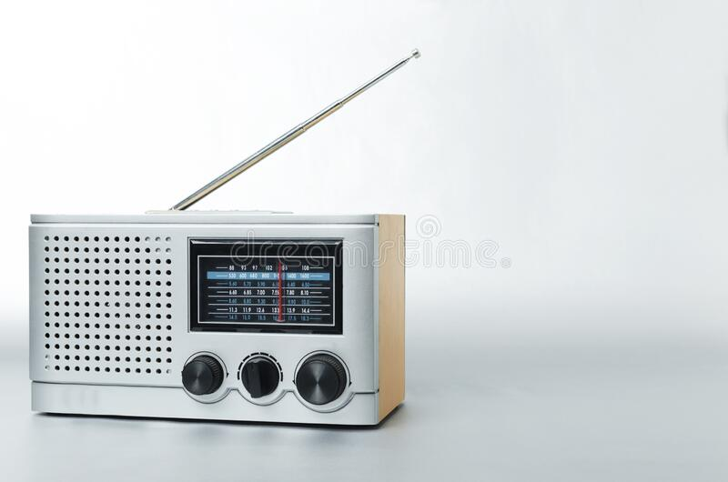 Old type of radio with fm channels and antenna on the gray background. Top view of retro radio and earphones on the grey surface.Concept of music adn different stock images