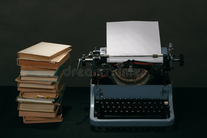 Old typewriter with books retro colors on the desk stock photography