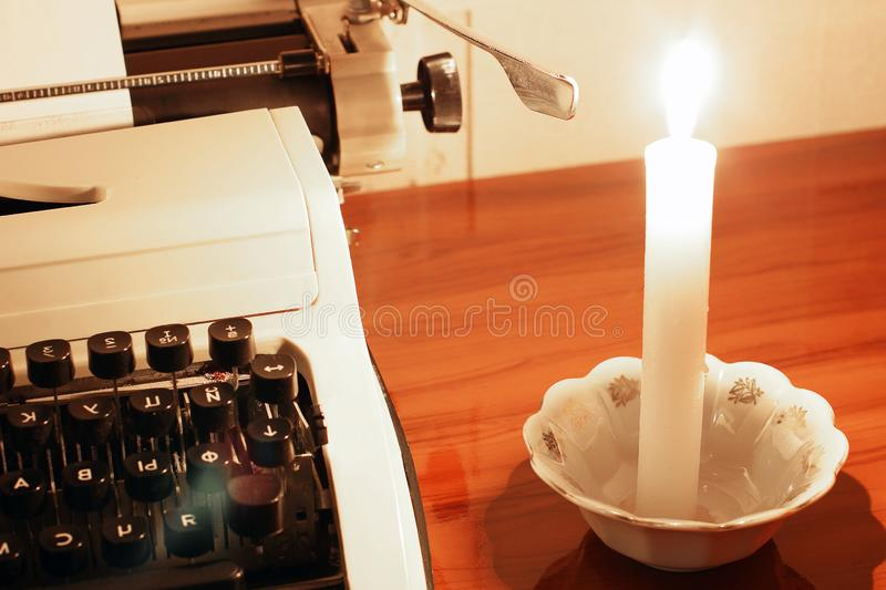 Old typewriter and burning candle.  stock images