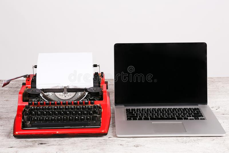 Old typewriter maschine and laptop on table. Concept of technology progress. An old red typewriter and a gray notebook on the desk. The concept of technology royalty free stock image