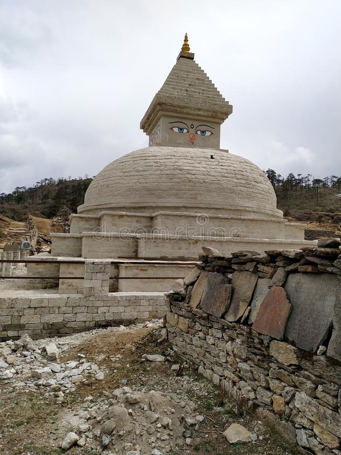 Old typical white Buddhist stupa in Himalaya mountains in cloudy weather stock images