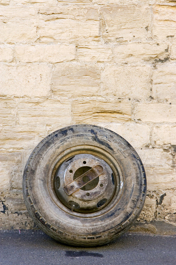 An old tyre leaning against a wall by the roadside royalty free stock photo