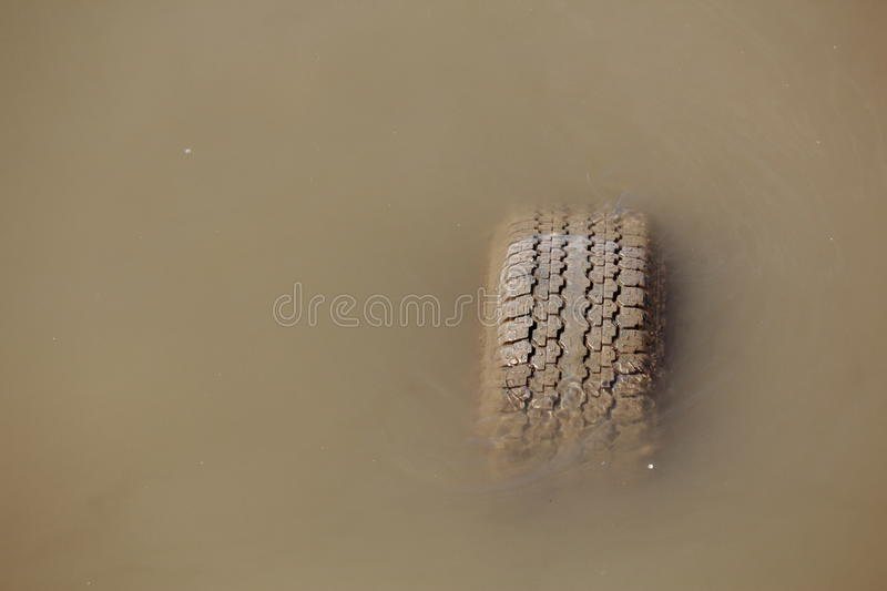 Old Tyre Sinking In The Water stock photography
