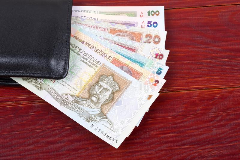 Old Ukrainian money in the black wallet. On a wooden background stock photos