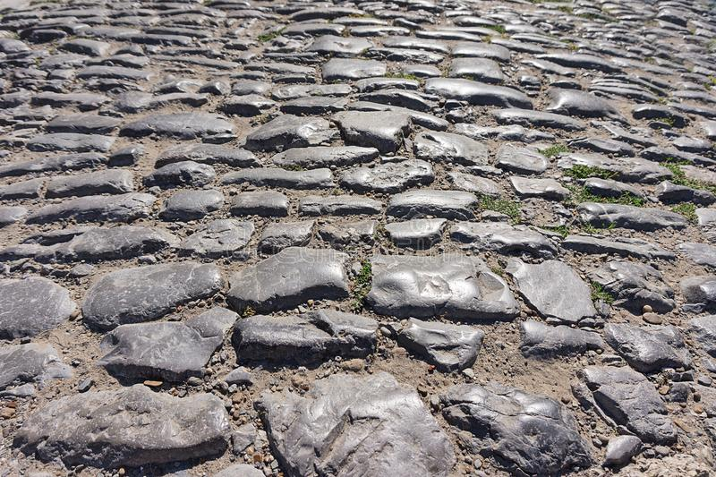 Old stones on paved road. Old uneven stones on a paved road royalty free stock image