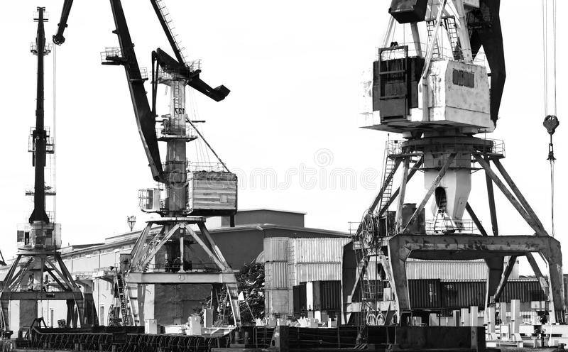The old unloading cranes at the port. Contrasting black-and-white photo royalty free stock photo