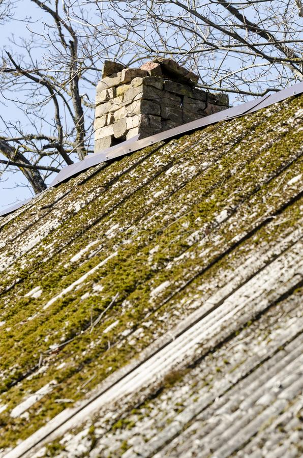 Unsafe roof with broken-down chimney. Old unsafe asbestos roof overgrown with moss with broken-down chimney stock photo
