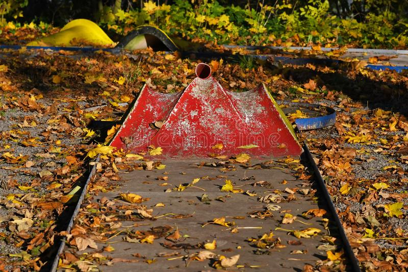 Untended miniature golf course with very chipped red paint covered in autumn leaves stock image