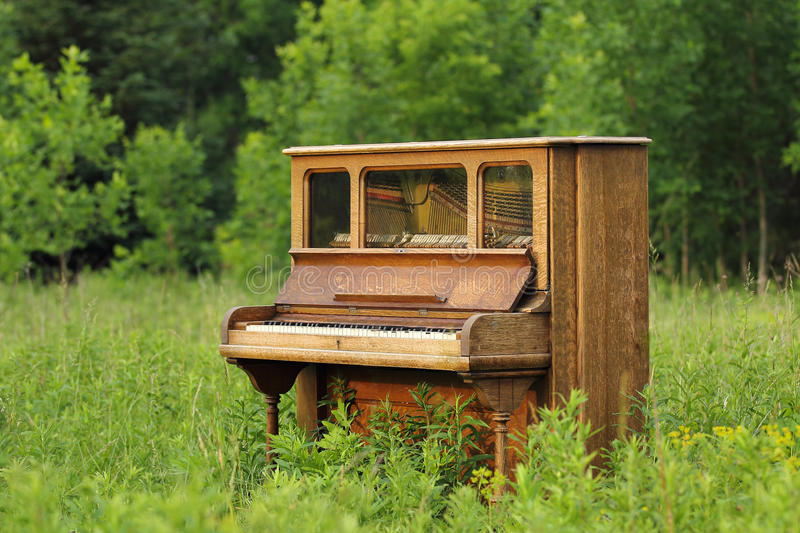 Old Upright Piano Abandoned in a Green Field. Old upright wood piano that has been abandoned in a green field / meadow / prairie royalty free stock image