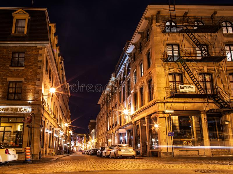 Old urban architecture of Montreal culture patrimony. Small street and historical buildings in the historic site of Old Port from. Montreal, night view. Scenic royalty free stock photo