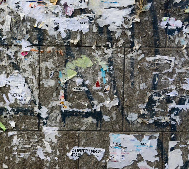 Old Urban Dirty Concrete Wall With Torn Worn Peeled Paper Poster, ADS. And Sticker Vertical Background Texture. Abstract Creative Surface royalty free stock photography