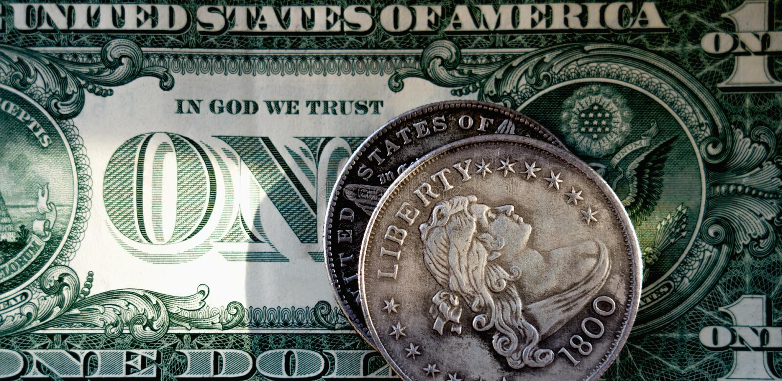 Old US coin with inscription: Liberty against coat of arms of the United States on one Dollar bill as symbol: America - the land stock photo